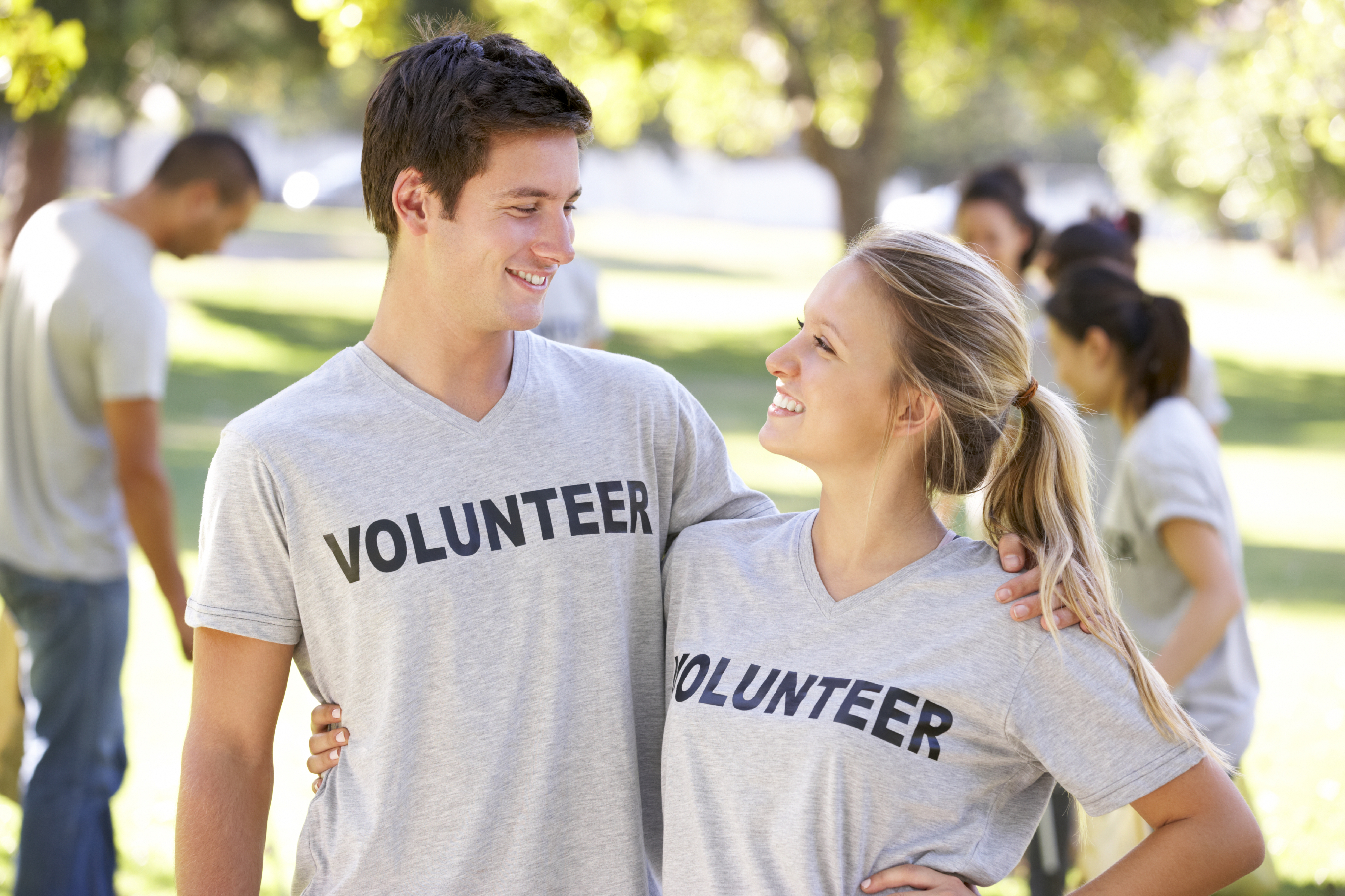 Two people wearing volunteer shirts hugging each other